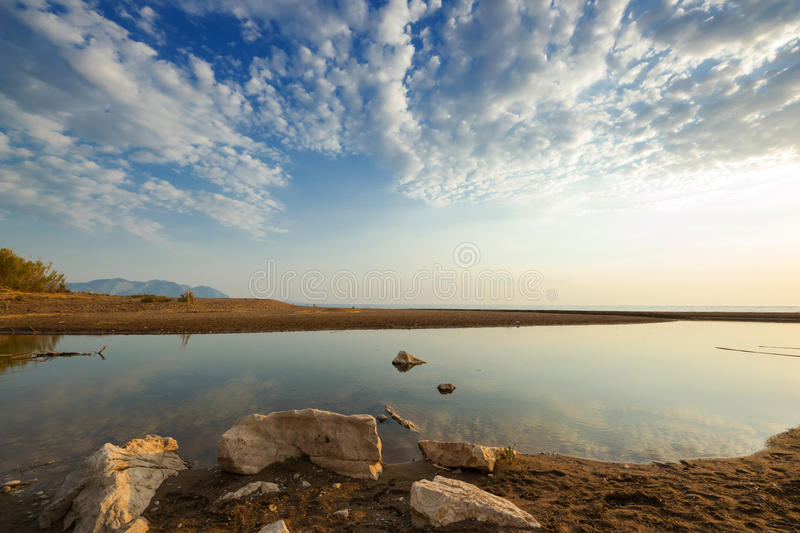 Estuary of a small river on a sandy beach, Greece. Estuary of a small river on a sandy beach at the sunset. Neda river at western Peloponnese, Greece royalty free stock images