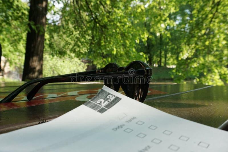 Estudando com um livro no parque, óculos de sol na tabela imagens de stock