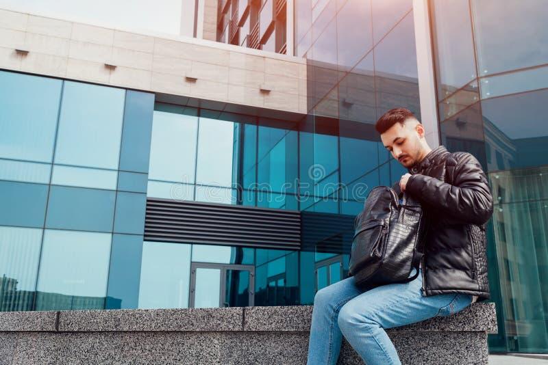 Estudante árabe que procura um telefone na trouxa fora Homem novo que senta-se pelo centro de negócios moderno fotos de stock royalty free