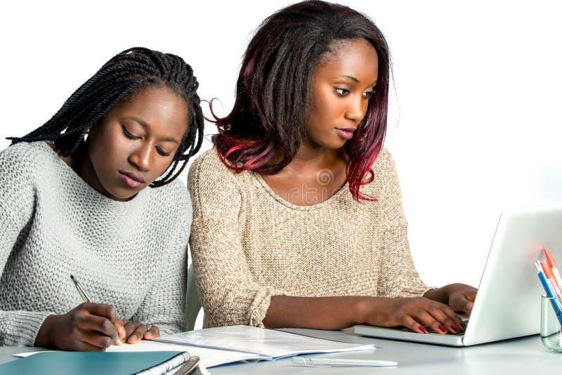 Estudante adolescente africano bonito que trabalha no portátil com amigo imagens de stock