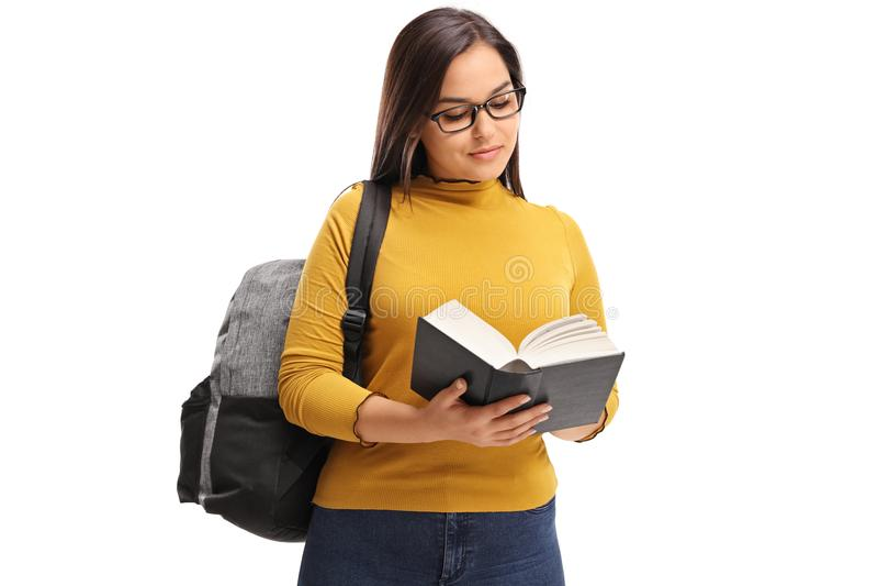 Estudante adolescente fêmea com uma trouxa que lê um livro fotografia de stock royalty free
