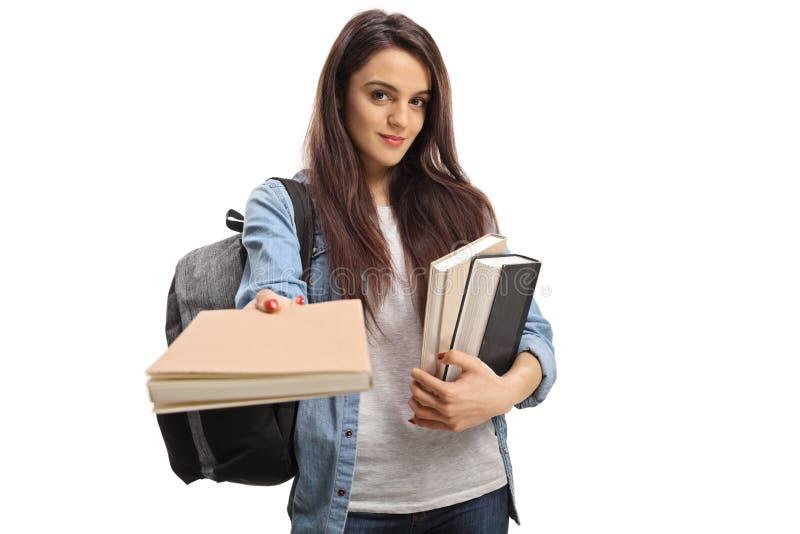 Estudante adolescente fêmea que dá um livro imagens de stock