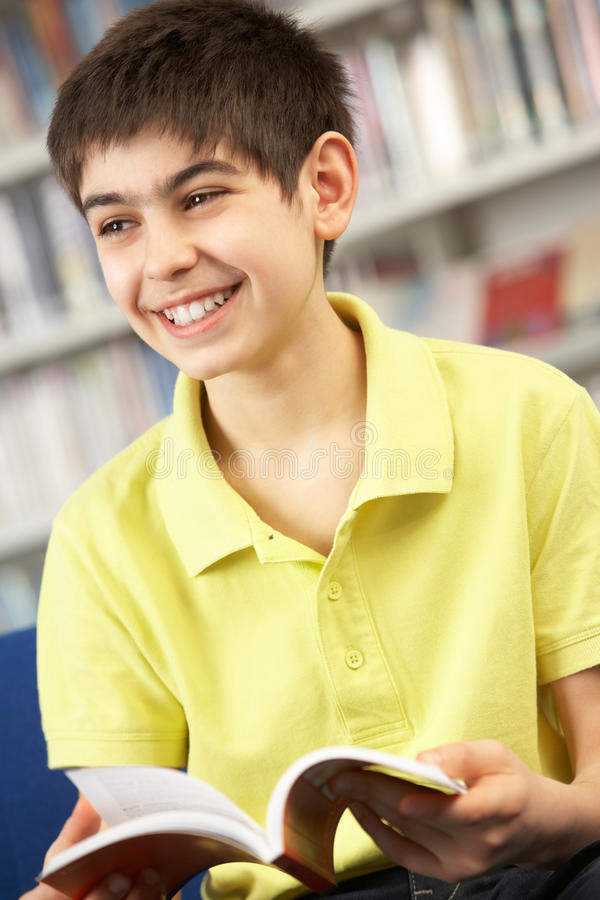 Estudante adolescente masculino no livro de leitura da biblioteca imagem de stock royalty free
