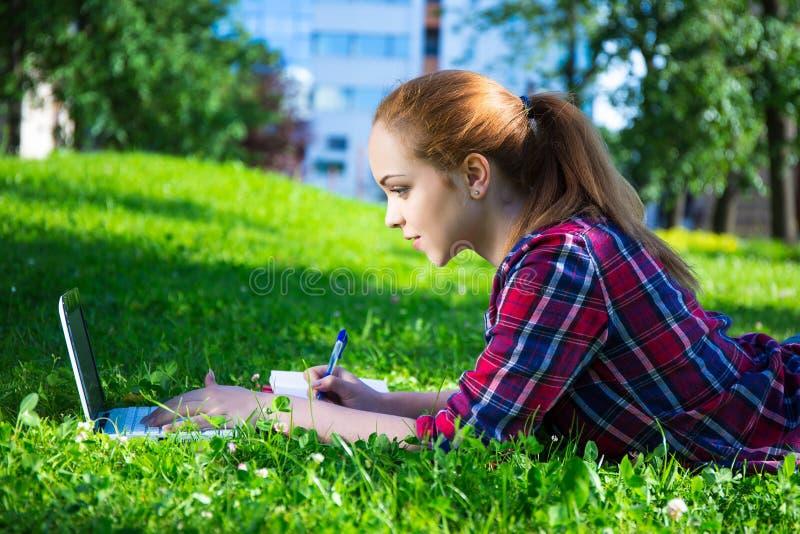 Estudante adolescente ou menina da escola que encontra-se no parque com portátil imagens de stock royalty free