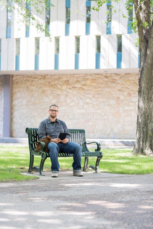 Estudante adulto meados de Sitting On Bench no terreno fotos de stock royalty free