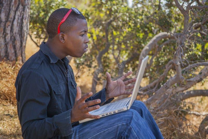 Estudante africano de sorriso que usa um portátil fotografia de stock