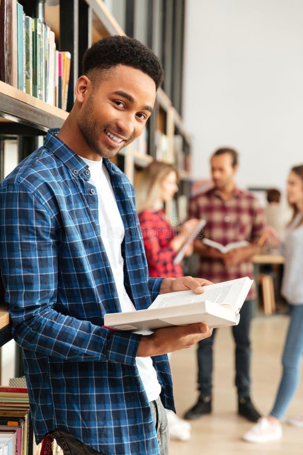 Estudante africano feliz novo do homem que está no livro de leitura da biblioteca foto de stock