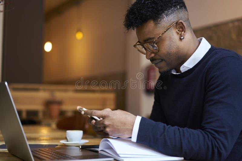 Estudante afro-americano da escola de negócios na camiseta escura e livros de leitura brancos da camisa e o funcionamento no port foto de stock royalty free