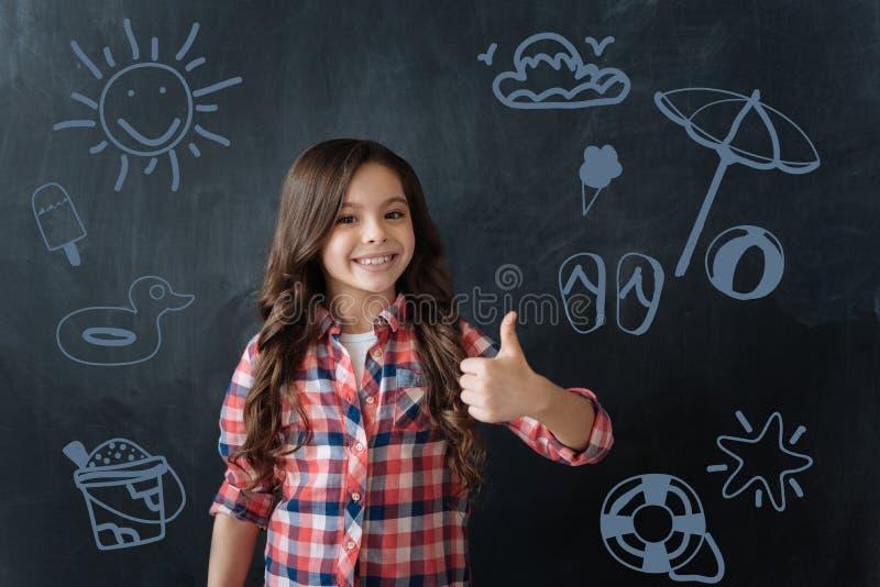 Estudante alegre que coloca seus polegares e que sonha sobre o verão imagens de stock