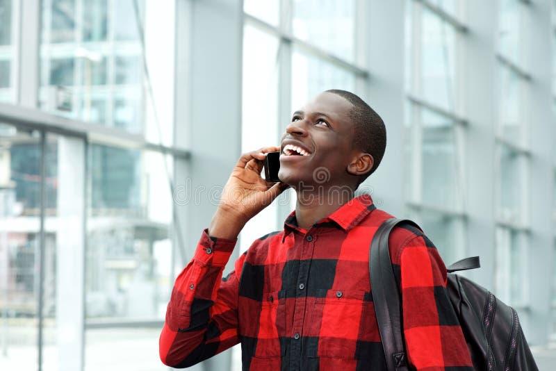 Estudante alegre que fala no telefone celular na estação fotografia de stock
