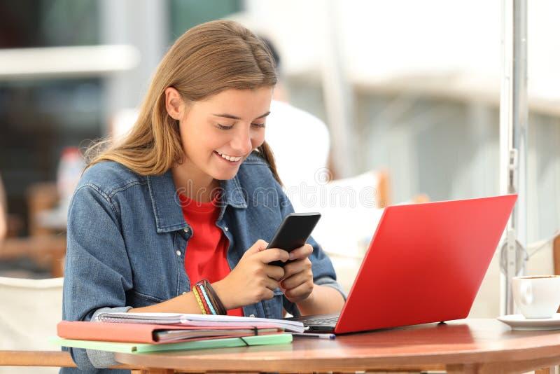 Estudante alegre que texting no telefone em uma barra fotos de stock