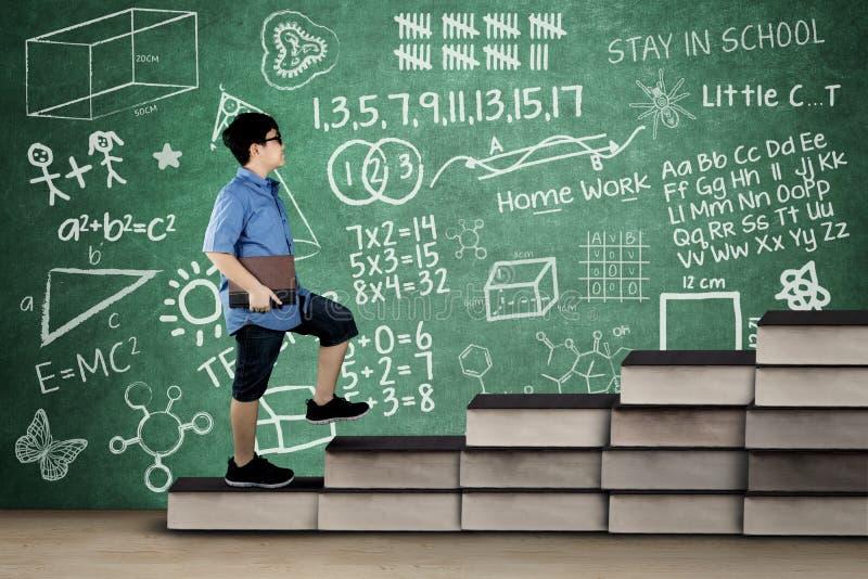 A estudante anda na escada dos livros com garatuja foto de stock royalty free