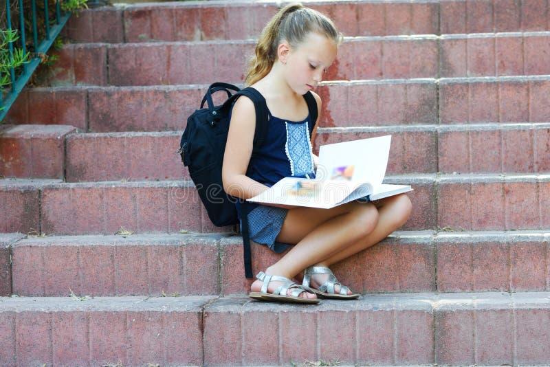 A estudante 8 anos de trabalhos de casa fazendo velhos em escadas lê o livro imagem de stock royalty free