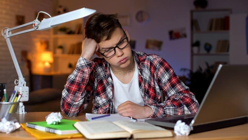 Estudante ansioso do adolescente que tenta resolver a atribui??o dif?cil da matem?tica, problemas foto de stock