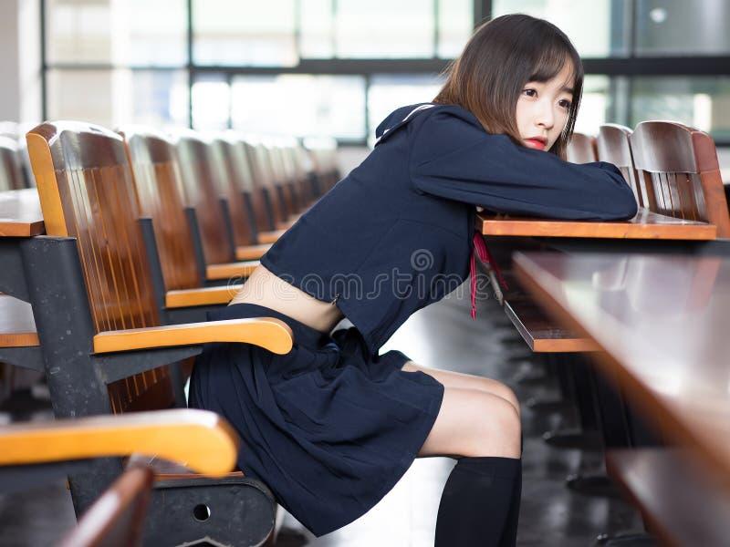 Estudante asiática na farda da escola que aprende na sala de aula imagem de stock royalty free