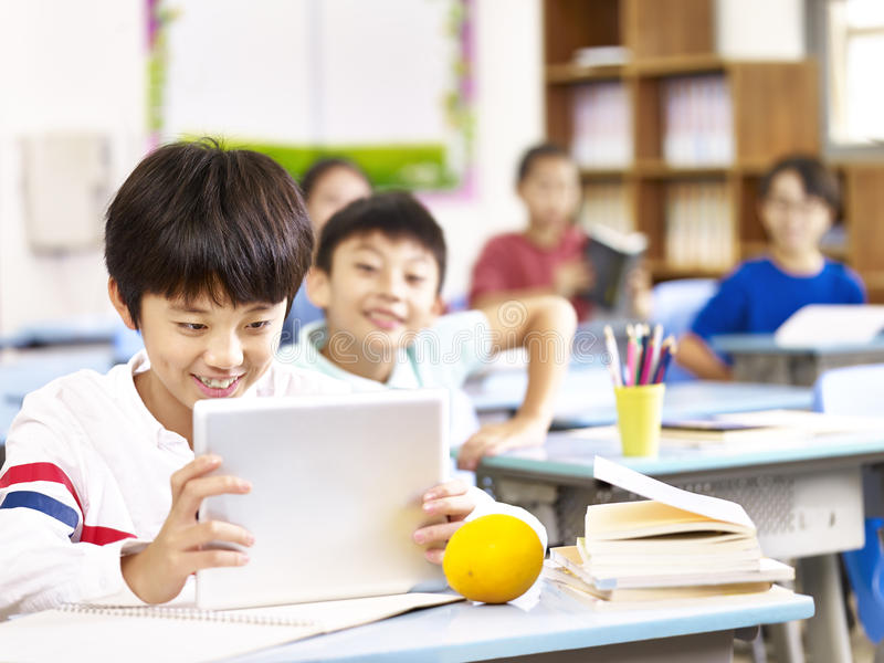 Estudante asiática que usa a tabuleta na sala de aula fotografia de stock