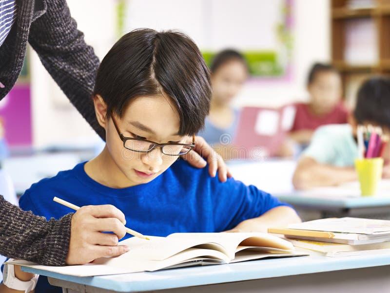 Estudante asiático da escola primária que obtém a ajuda do professor imagem de stock