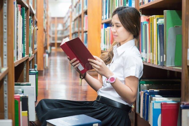Estudante asiático na leitura uniforme na biblioteca na universidade fotos de stock