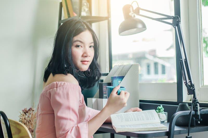Estudante asiático novo com abertura e leitura da xícara de café de um livro na tabela de madeira em casa foto de stock