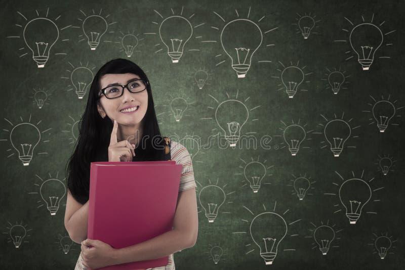 Estudante asiático que pensa das ideias na classe em desenhos da ampola imagem de stock royalty free