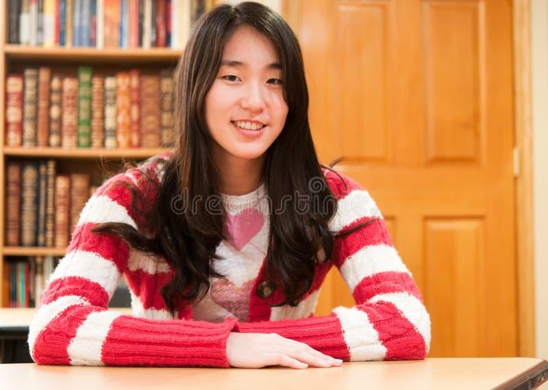 Estudante asiático que senta-se na mesa na sala de aula imagens de stock royalty free