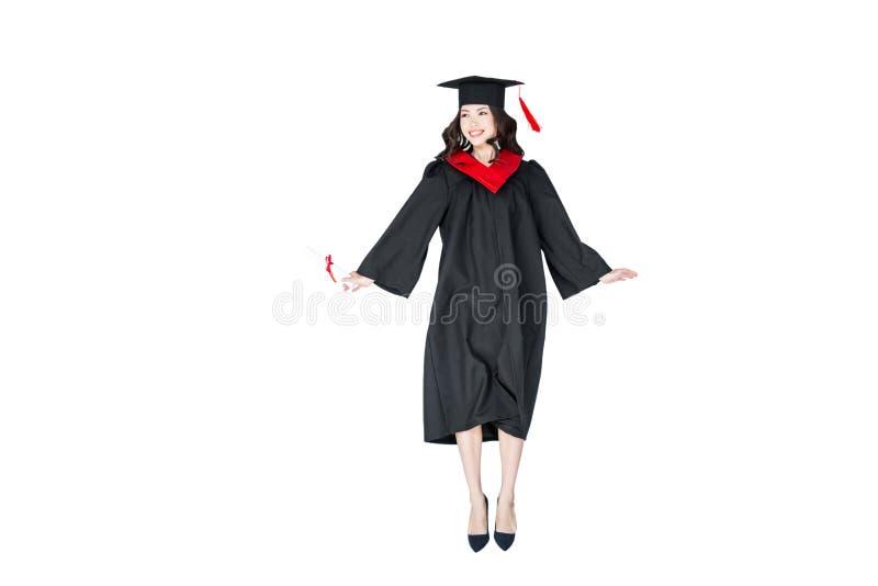 Estudante atrativo no tampão da graduação com salto do diploma isolado foto de stock royalty free