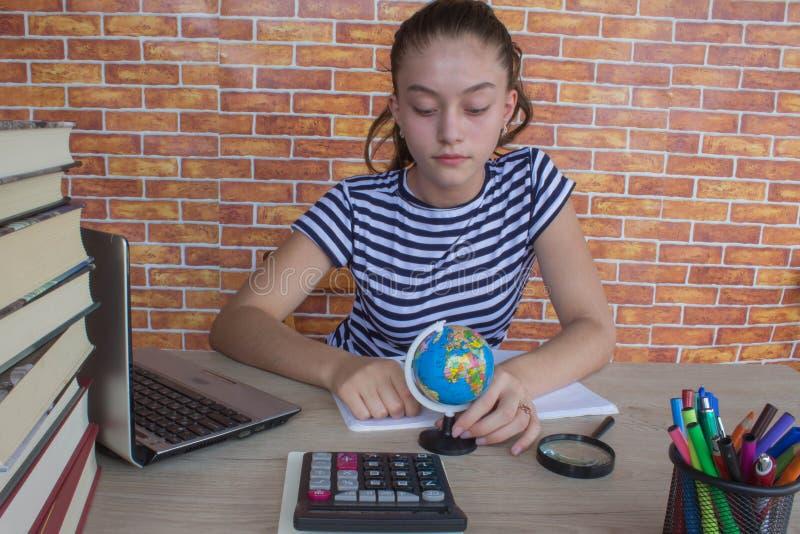 estudante atrativo novo Girl que estuda lições Moça que senta-se na mesa em casa, fazendo trabalhos de casa fotografia de stock royalty free