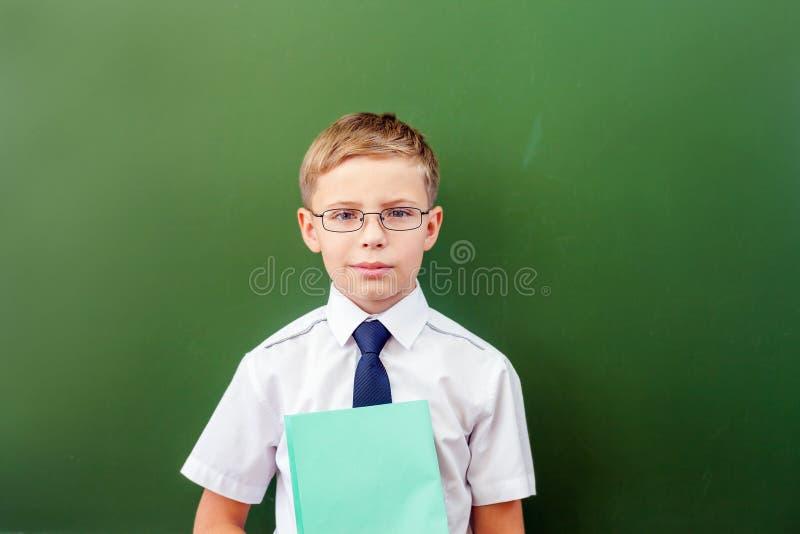 Estudante bem sucedida que está perto do quadro-negro na sala de aula da escola fotografia de stock royalty free