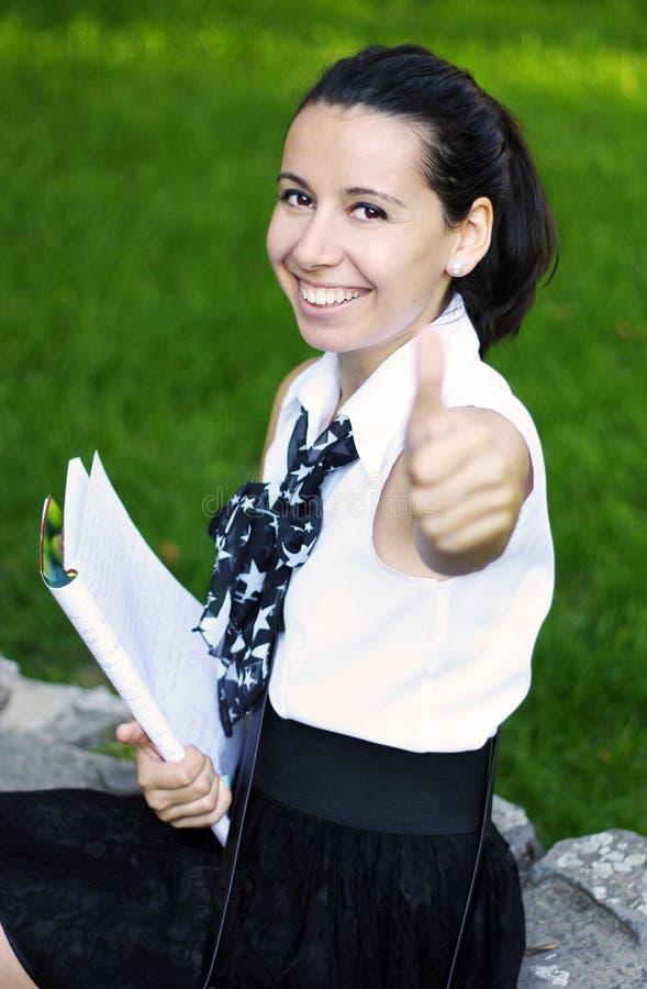 Estudante bem sucedido feliz que mostra o sinal aprovado foto de stock