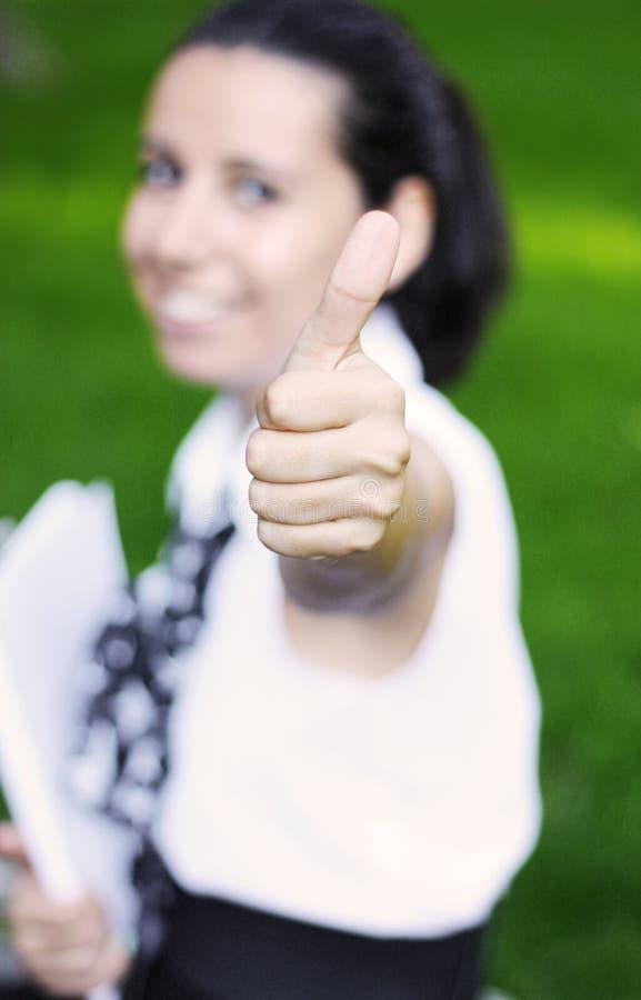 Estudante bem sucedido feliz que mostra o sinal aprovado fotografia de stock