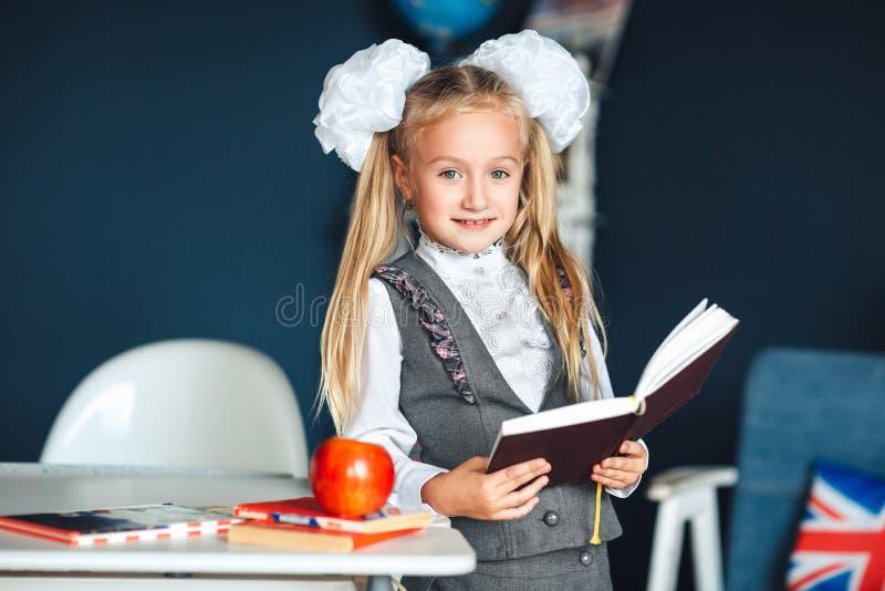 Estudante blondy na farda da escola com as curvas brancas que estão perto da tabela e que estudam na sala de aula Educa??o e esco fotos de stock royalty free