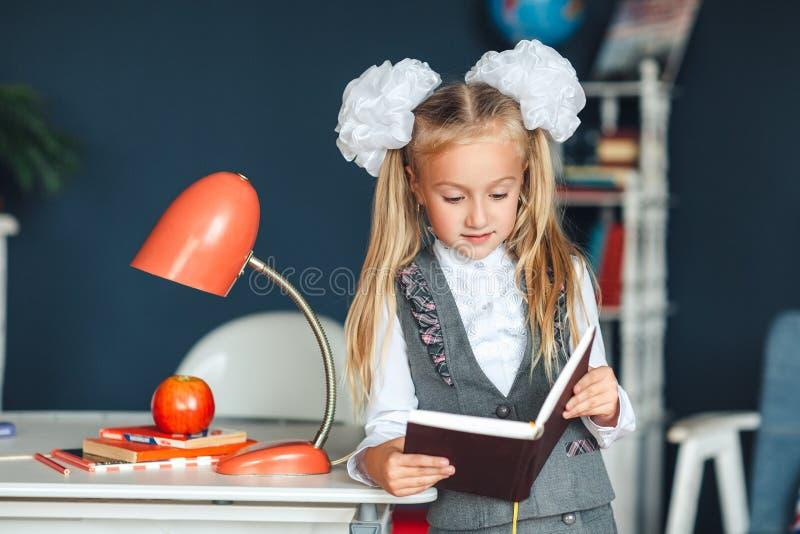 Estudante blondy na farda da escola com as curvas brancas que estão perto da tabela com lâmpada e Apple vermelhos e que estudam e imagens de stock