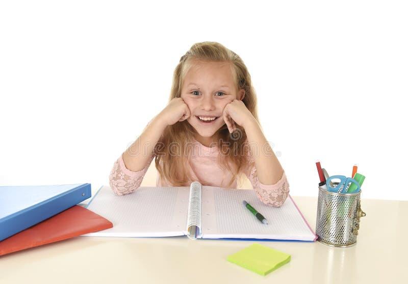 Estudante bonita com assento feliz de sorriso do cabelo louro na mesa que faz trabalhos de casa isolada no branco foto de stock