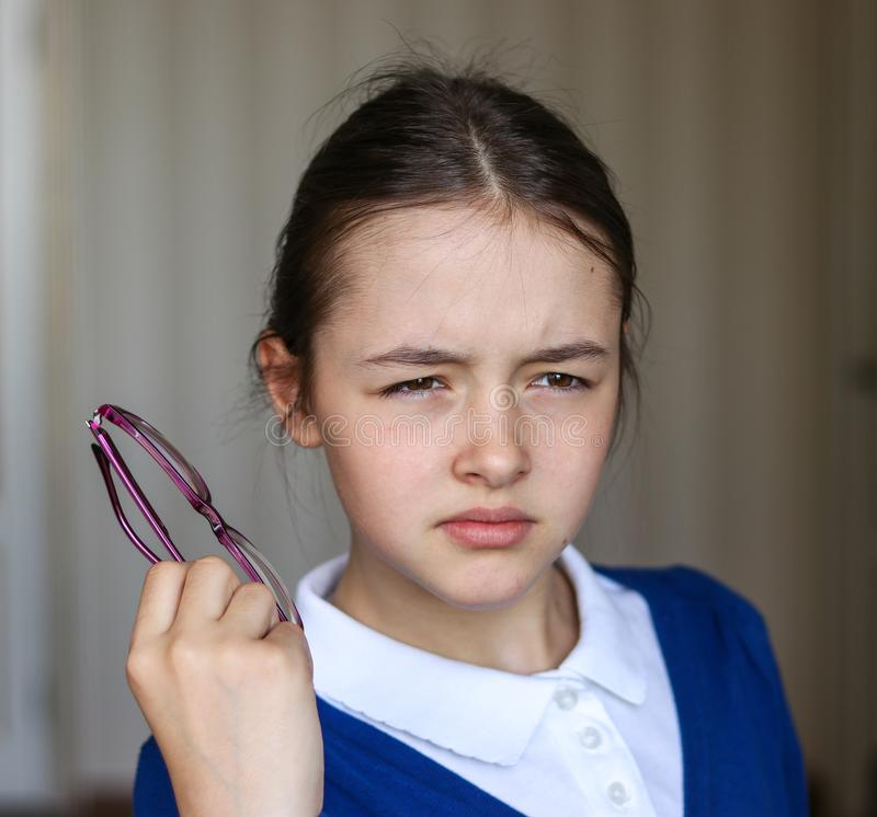 Estudante bonita na farda da escola que parafusa acima de seus olhos que tentam ver algo sem vidros imagem de stock royalty free