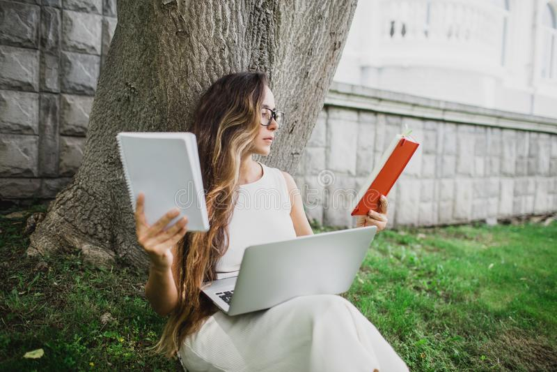 Estudante bonita que aprende suas lições que sentam-se na grama fotos de stock royalty free