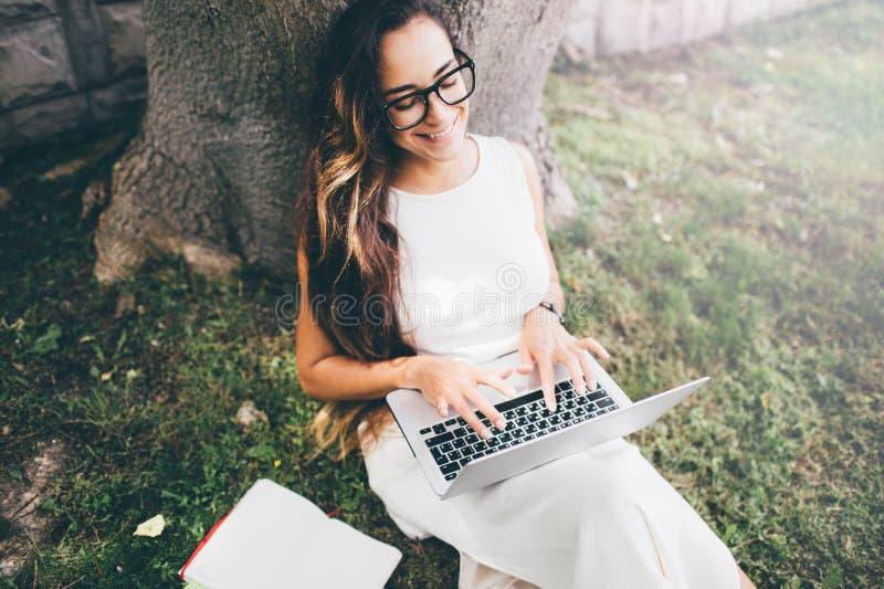 Estudante bonita que aprende suas lições que sentam-se na grama foto de stock royalty free