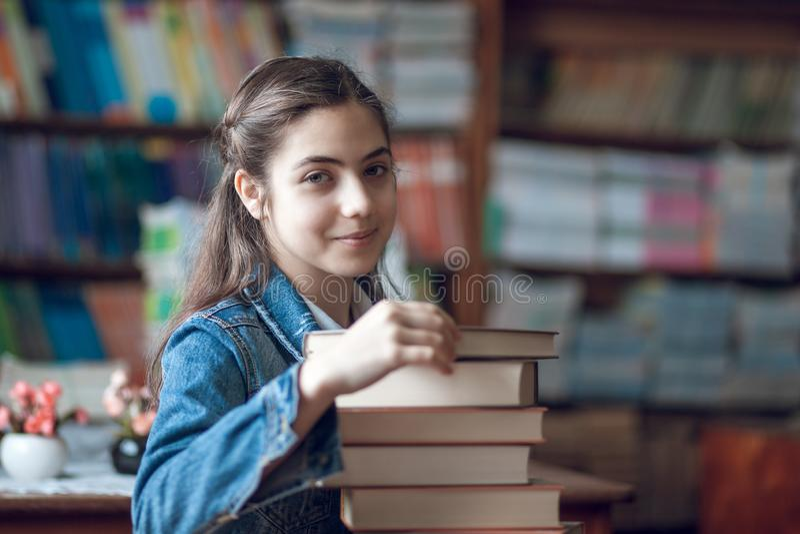 Estudante bonita que senta-se na biblioteca com livros imagem de stock royalty free