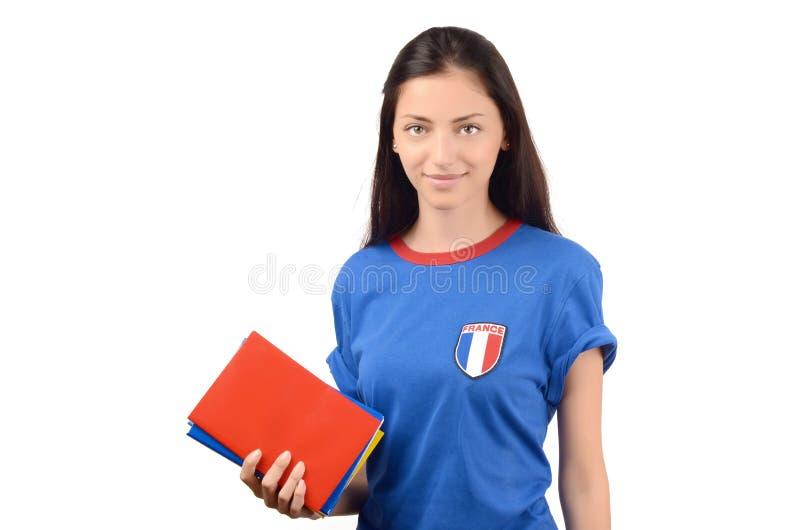 Estudante bonito com a bandeira de França na blusa azul que guarda livros, livro vermelho vazio da tampa fotos de stock royalty free