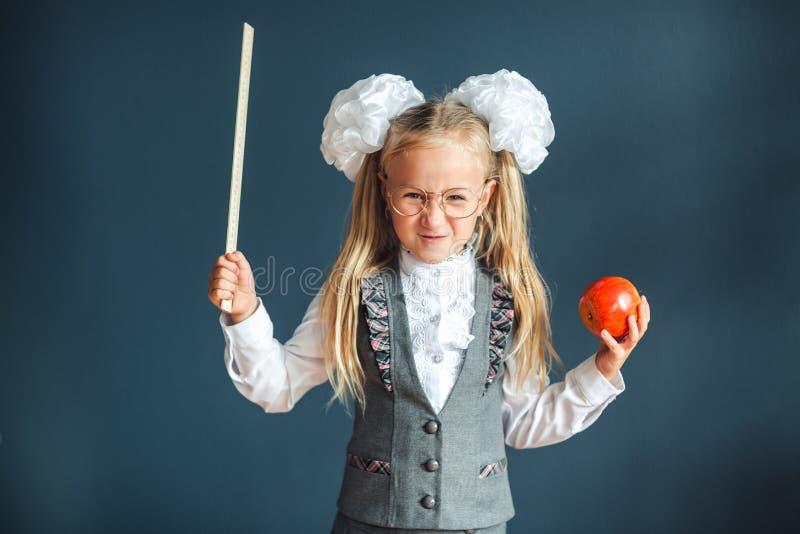 A estudante bonito com os vidros e Apple vermelho à disposição que olham como um professor restrito aumentou seu ponteiro para ti fotografia de stock royalty free