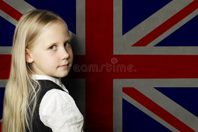 Estudante bonito da criança contra o fundo BRITÂNICO da bandeira Conceito da escola de l?ngua inglesa fotos de stock