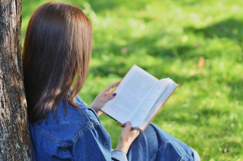 Estudante bonito, feliz da moça que lê um livro que senta-se na grama verde sob uma árvore perto do terreno, universidade, escola imagem de stock royalty free