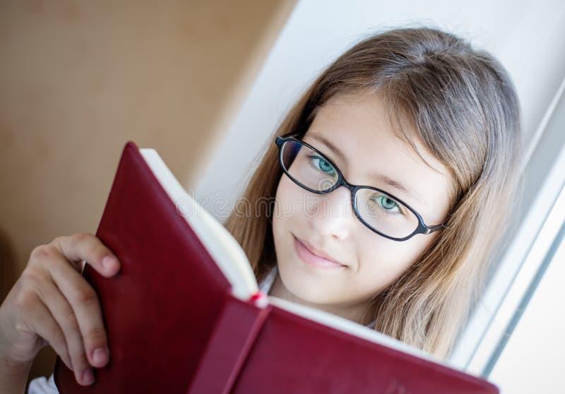 Estudante bonito nos vidros que guardam um livro fotos de stock