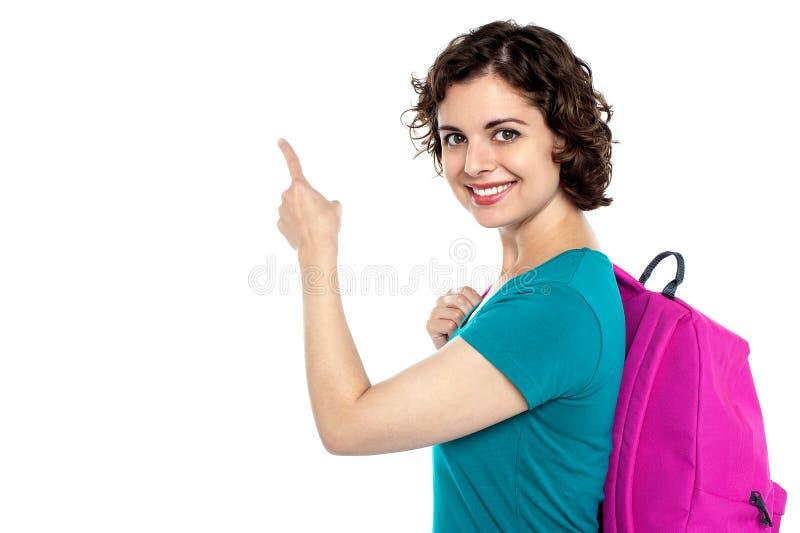 Estudante bonito que indica para a área de espaço da cópia foto de stock royalty free