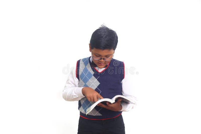 Estudante bonito que lê um livro seriamente ao vestir os vidros, isolados no fundo branco fotografia de stock royalty free
