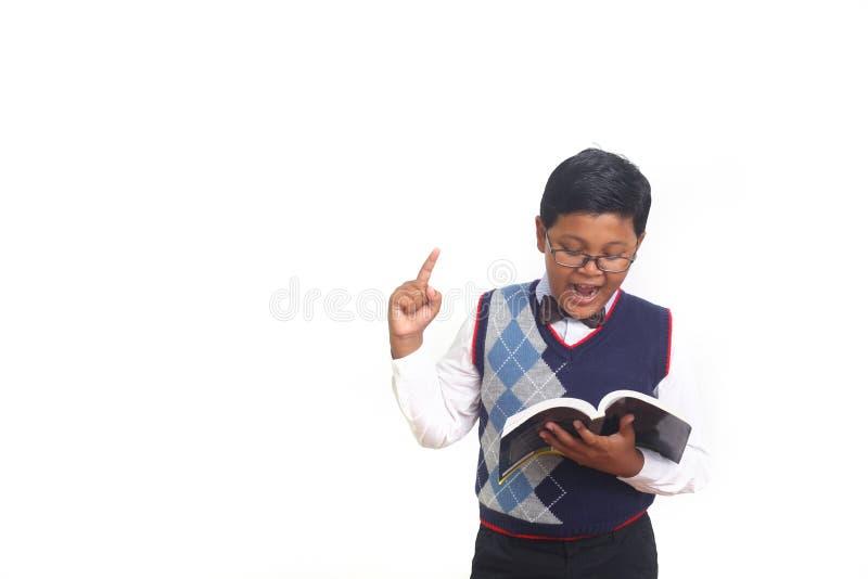 Estudante bonito que obtém uma ideia ao vestir vidros e ao guardar um livro, isolado no fundo branco fotos de stock
