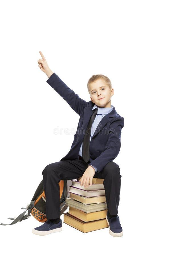 Estudante bonito que senta-se em livros e que mostra o polegar acima, isolado no fundo branco foto de stock