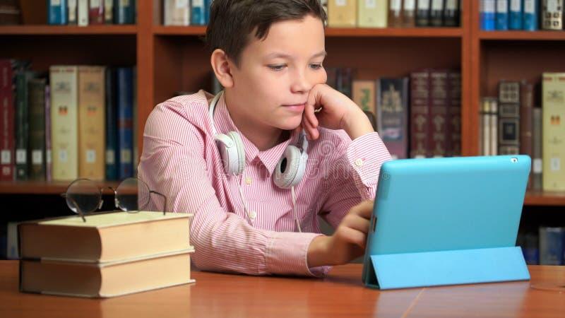 Estudante bonito que usa a tabuleta do computador e escutando ela leitura imagem de stock