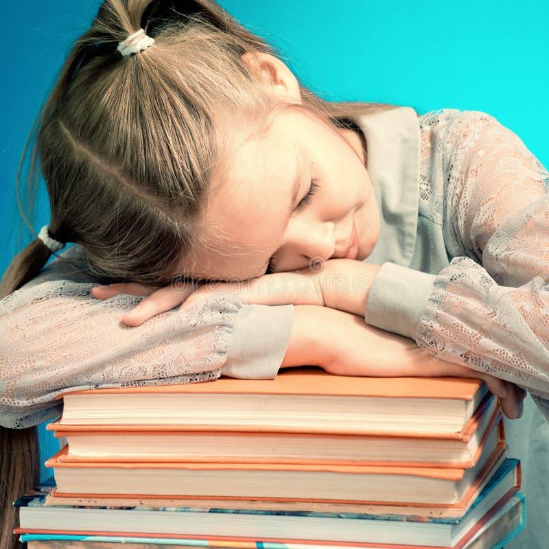A estudante caiu sono em uma pilha de livros ing um livro no fundo azul foto de stock