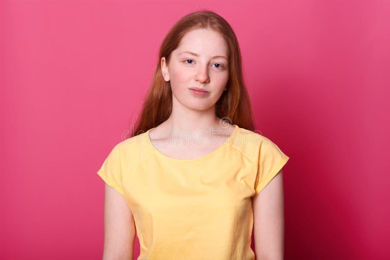 A estudante calma da aparência delicada, levantando naturalmente no estúdio apenas, olha na câmera sobre o fundo cor-de-rosa char fotos de stock