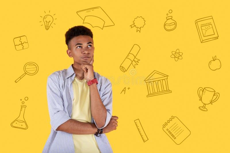 Estudante calmo que toca em sua cara e que pensa sobre a vida após a graduação imagem de stock